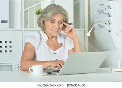woman sitting at table with laptop