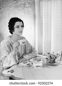 Woman sitting at a table with a tea cup in her hand
