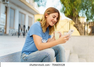 Woman sitting, taking a lemonade on stairs, casual photo.