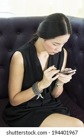 Woman sitting text messaging on a mobile phone