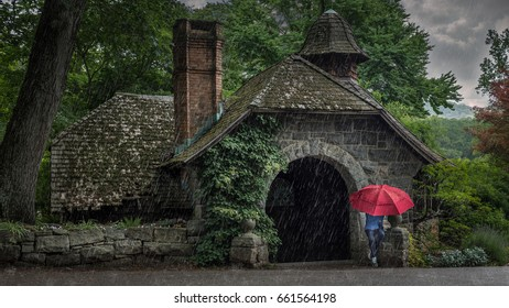 Woman sitting under a red umbrella on a rainy day in front of the old stone pump house at the New Jersey Botanical Gardens in Ringwood, NJ