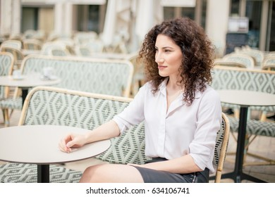 A woman is sitting and waiting for a coffee