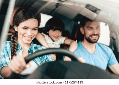 A Woman Is Sitting At The Wheel Of A New Vehicle. Smiling Family. Car Buying In A Showroom. Automobile Salon. Cheerful Driver. Happy Together. Successful Buying. Good Mood. Great Trade.