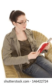 a woman sitting in a wicker chair reading a book