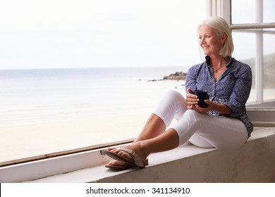 Woman Sitting At Window And Looking At Beautiful Beach View