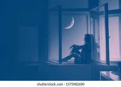 Woman sitting at the window looking at stars and the moon, Artistic Photography meditation and dreaming concept