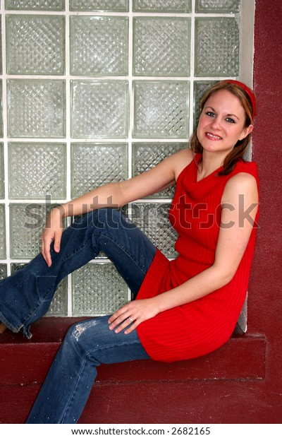 Woman sitting in a windowsill in red dress