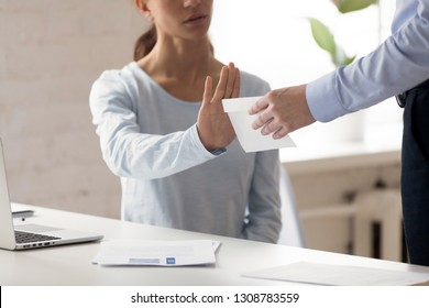 Woman sitting at workplace refuse money in the envelope offered by dishonest man, want to bribe employee for receiving something in exchange, cropped close up view. Anti bribery and corruption concept