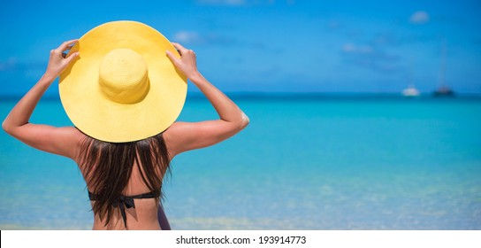 Woman sitting in yellow hat on white sand beach enjoying summer vacation