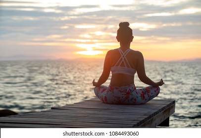 woman sitting in yoga meditating pose at sea side against beautiful sun rising sky