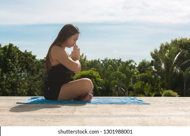 Woman sitting in a yoga pose outdoor. Peaceful zen.