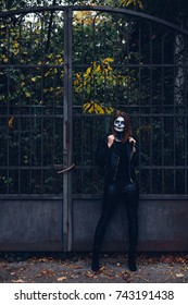 Woman in Skeleton costume waiting outside the iron gate