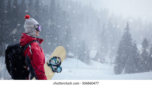 Woman in ski suit over winter background, snowboarding, winter sport