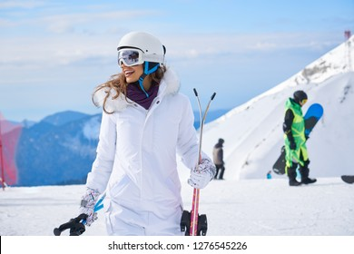 woman skier close up portrait wearing white healmet with mask in snow winter mountain