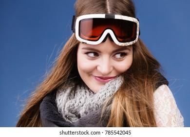 Woman skier girl wearing warm clothing ski googles portrait. Winter sport activity. Beautiful sportswoman on blue studio shot