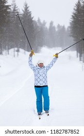 Woman skier has overcome distance in wood, screaming and holding up ski poles, blizzard