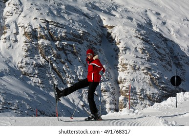 woman skier in a red ski equipment in the Alps ,  Cortina d'Ampezzo , Italy