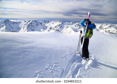 Woman skier standing on snow covered summit, Les Deux Alpes, France