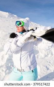 Woman skier in a white suit mountain top in snow