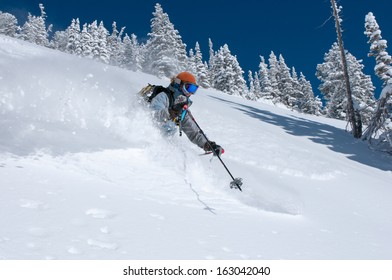 Woman skiing deep powder snow on a perfect winter day