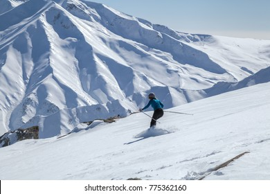 A woman skiing downhill on snow covered Himalayan Mountain in Gulmarg, Jammu and Kashmir, India