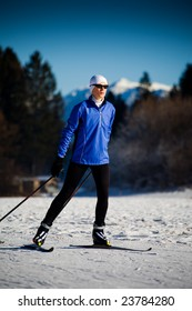 A woman skiing in the mountains. Nordic or skate style.