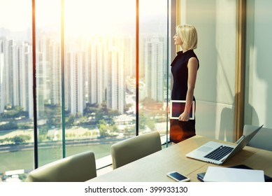 Woman skilled employer with touch pad in hand is looking in office skyscraper window of conference room while is thinking that adopt a decision after interview with specialists in the economic sphere
