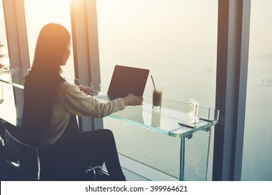 Woman skilled managing director is working on laptop computer with blank copy space screen for your advertising content, while is sitting in modern co-working space during her business trip in China