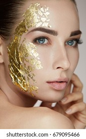 Woman Skin Care. Portrait Of Young Female Model With Beauty Gold Mask Touching Facial Fresh Skin.
