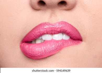 woman skin, closeup biting lips, bright teeth, open mouth, natural lip lipstick color