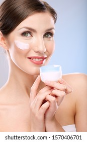 Woman with skin cream on face. Girl holding white jar. isolated beauty portrait.