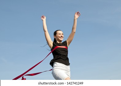 woman in skirt crossing finishing line