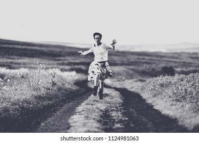 Woman in skirt running on a countryside road. Freedom concept. Black and white, toned, vintage effect