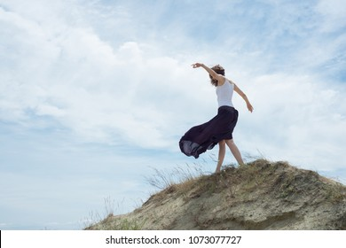 Woman in a skirt walks through the mountain