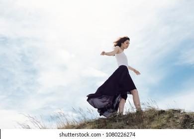 Woman in a skirt walks through the mountain