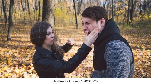 A woman slaps a man in the face. An emotional male is getting slapped in face, crouching his face with closed eyes in a fear.