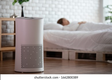 woman sleep with Air purifier in cozy white bedroom for filter and cleaning removing dust PM2.5 HEPA in home,for fresh air and healthy life,Air Pollution Concept