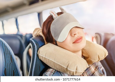 Woman in sleep mask and with pillow travelling in bus