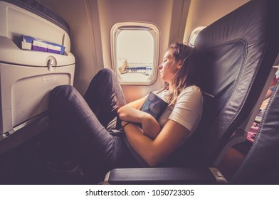 Woman sleeping in an airplane. holding a book. Passenger relaxes at a window in a flying aircraft after reading a book