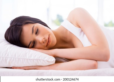 Woman sleeping. Beautiful young smiling woman sleeping in bed