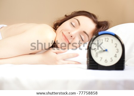 Woman sleeping in bed and alarm-clock  (focus on woman)