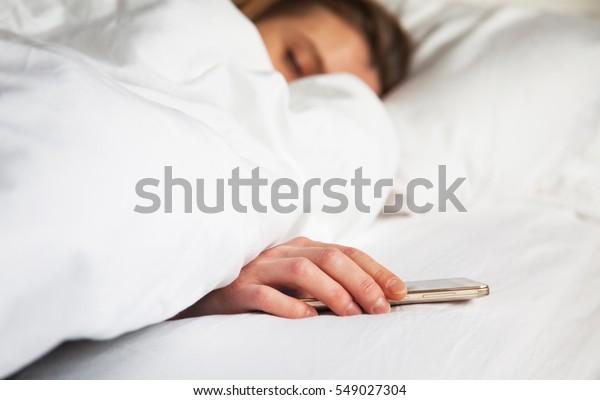 携帯電話で起こされるベッドで眠っている人