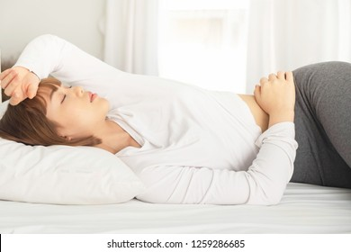 A woman sleeping in bed, head resting on a pillow with hands beside her head. And a quilt covering up to her shoulder, comfortably and blissfully. Sunbeam dawn on her face