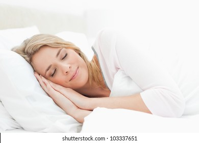 A woman sleeping in bed, her head resting on a pillow with her hands beside her head. And a quilt covering up to her shoulder.