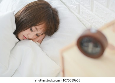 Woman sleeping in bed peacefully at home beside alarm clock
