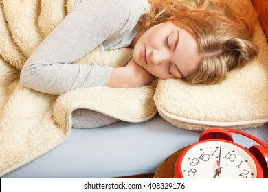 Woman sleeping in bed under wool blanket with set alarm clock. Girl relaxing napping in morning. Female about to wake up.