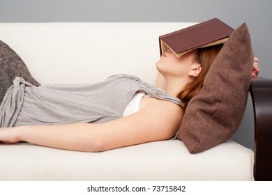 woman sleeping with book on her face