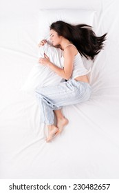 Woman sleeping in fetal position with pillow