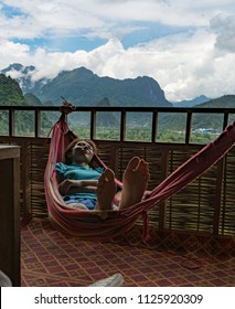 A woman sleeping in a hammock, beautiful view, treehouse in the jungles of Laos