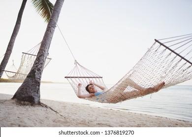 Woman sleeping in a hammock on an island with palm trees near the ocean